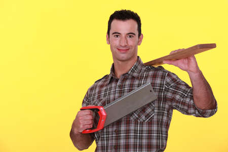 Builder holding a wooden plank and a saw photo