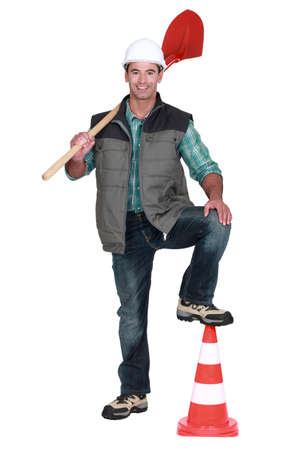 road worker holding a shovel and leaning his foot on a traffic cone photo