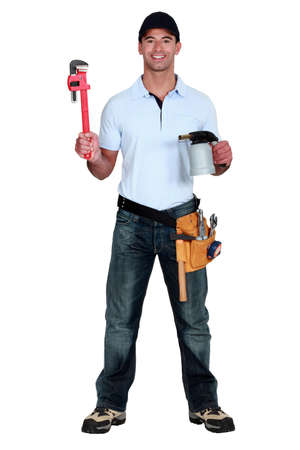 happy craftsman holding a spanner and a welding torch photo