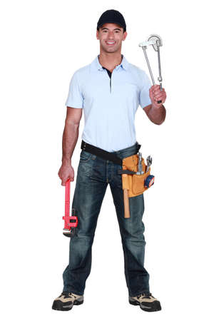 industrialized: Plumber holding pipe bending tool Stock Photo