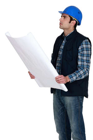 inconsistent: Construction worker verifying a building drawing