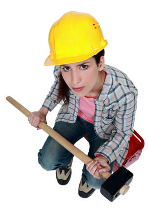 sledge hammer: female builder holding a sledge hammer