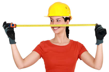 chirpy: Tradeswoman extending a measuring tape Stock Photo