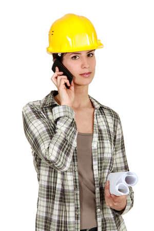 Tradeswoman using mobile phone photo