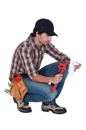 Plumber using a pipe wrench photo
