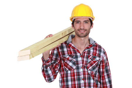 Tradesman carrying wooden planks photo