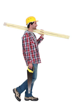 layman: Profile of a carpenter with wood and a saw
