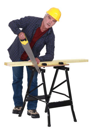 Tradesman sawing a wooden plank photo