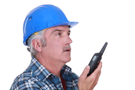 A foreman talking on a walkie-talkie. photo