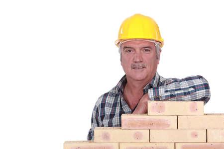 female elbow: Artisan leaning on stack of bricks