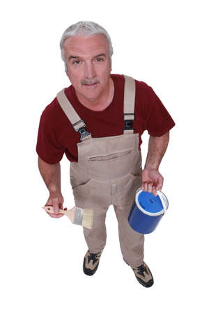 Middle-aged decorator holding paint tin and brush photo