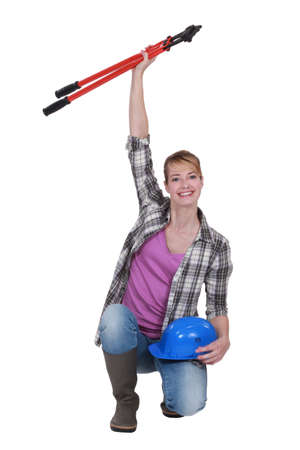 Tradeswoman holding a pair of large clippers in the air photo