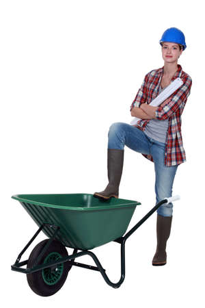 Tradeswoman with her foot propped on a wheelbarrow photo