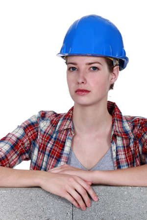 Female mason stood by unfinished wall photo