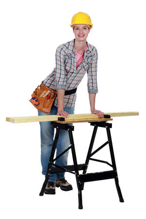 tradeswoman: Tradeswoman leaning against a workbench Stock Photo