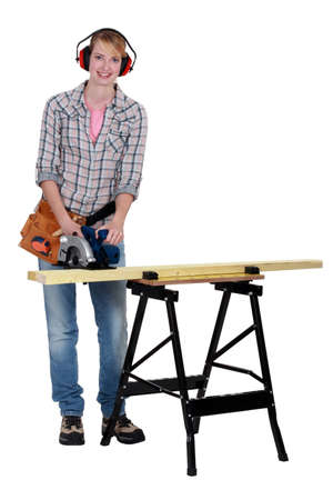 Woman using a circular saw to cut a wooden plank photo