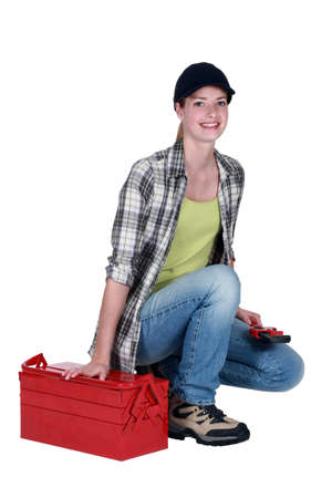 servicewoman: Woman kneeling by tool kit