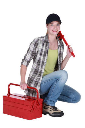 tool kit: Female plumber with wrench and tool kit