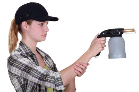 Woman holding blow-torch photo