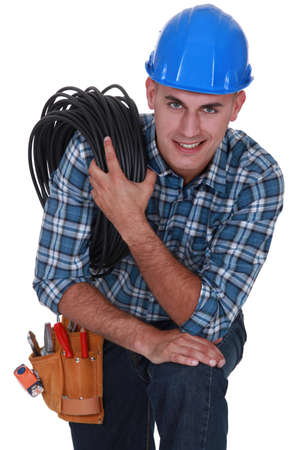 Tradesman carrying a cable coiled around his shoulder photo