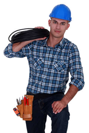 Electrician carrying spool of wiring photo