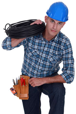 Electrician holding coil of cable over shoulder photo