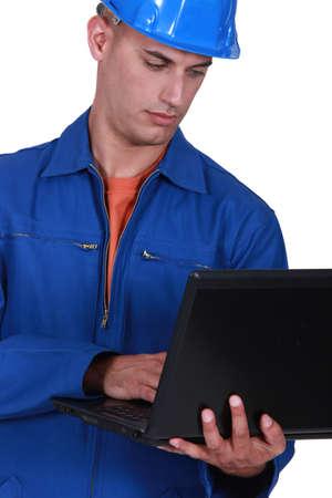 electricista: Fontanero con un ordenador portátil Foto de archivo