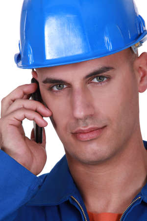boiler suit: Young worker in boiler suit making call Stock Photo