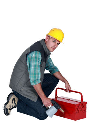 Workman with a blowtorch and toolbox photo
