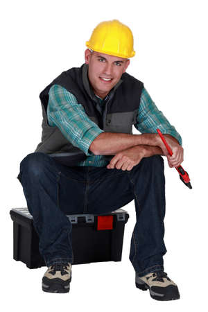 Workman sitting on a toolbox photo