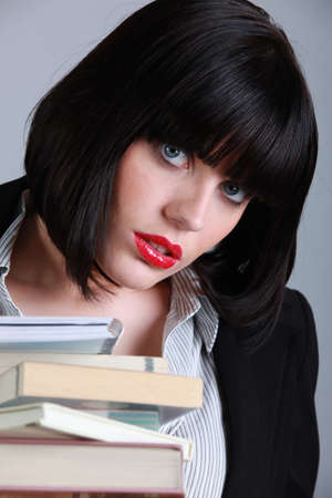 refused: Brunette woman with stack of books Stock Photo