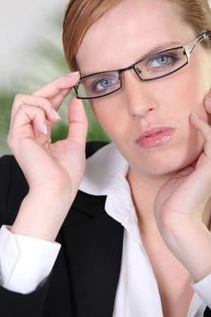 exacting: Businesswoman holding a pair of glasses Stock Photo