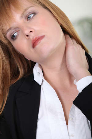 grabbing at the back: Closeup of a businesswoman with neckache