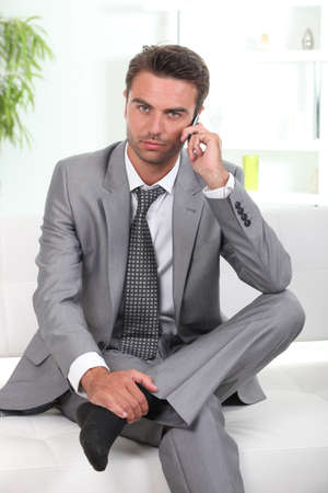 man in suit: Man in a suit talking on cellphone Stock Photo