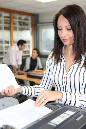 fotocopiadora: Una mujer utilizando una fotocopiadora de oficina