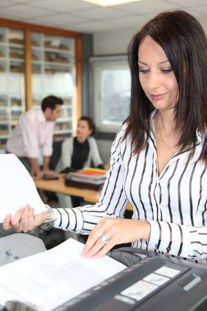 photocopier: Woman using an office photocopier