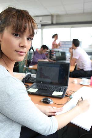 Woman in a busy office using a laptop and headset photo