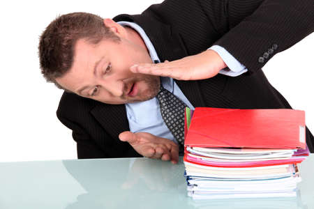Businessman examining his pile of work photo