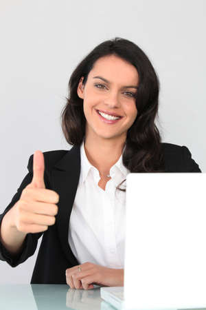 Businesswoman giving the thumbs up photo