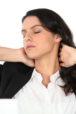 pain relief: Businesswoman rubbing her neck Stock Photo