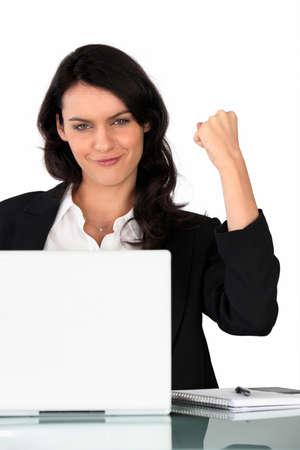 triumphant: Businesswoman holding a triumphant fist in the air