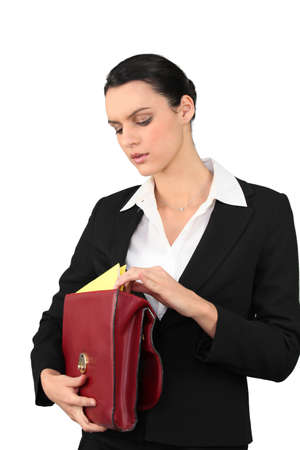 hair tied: business woman searching for a document in her briefcase