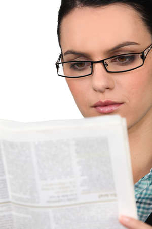 publisher: Young woman in glasses reading a newspaper