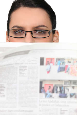 eyes hazel: Woman in glasses peering over a newspaper Stock Photo