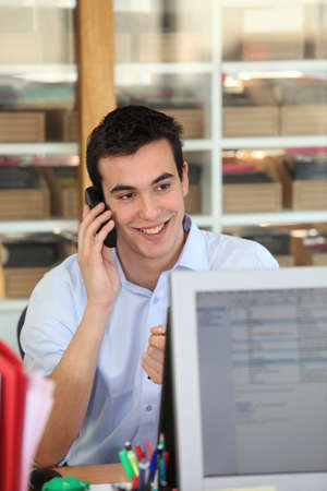 electronically: Male office worker speaking to customer on the telephone Stock Photo