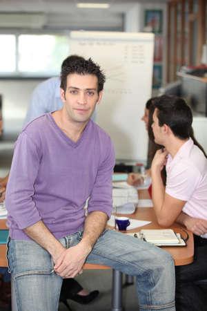 Man in jeans perching on an office desk photo