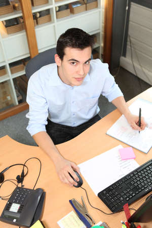 Young man working at an office desk photo