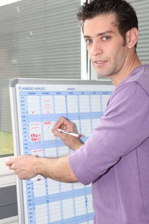 Man writing on a white board planner photo
