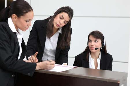 filling in: Businesswomen filling in paperwork Stock Photo