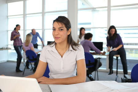 workplace wellness: Smiling woman using a laptop in a busy office Stock Photo